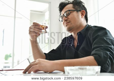 Alcohol addicted businessman is holding cigarette and whiskey glass while working. Sad depressed patient male adult having troubles. Asian Drunk man with Alcoholism. stock photo