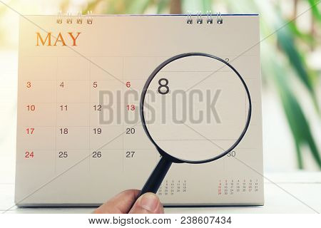 Magnifying glass in hand on calendar you can look Eighth day of month,Focus number eight in May,Concept in business and meetings. stock photo