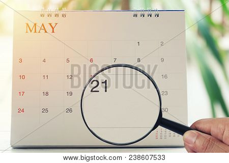 Magnifying glass in hand on calendar you can look Twentieth one day of month,Focus number twenty-one in May,Concept in business and meetings. stock photo