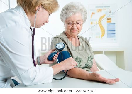 Female doctor measuring blood pressure of senior woman stock photo