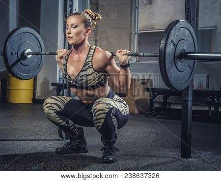 Athletic blond female fitness model holding heavy barbell and preparing for squats. stock photo