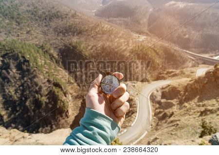 Close-up A man's hand holds a pocket compass against the backdrop of a mountain road and forest. The concept of outdoor navigation. stock photo