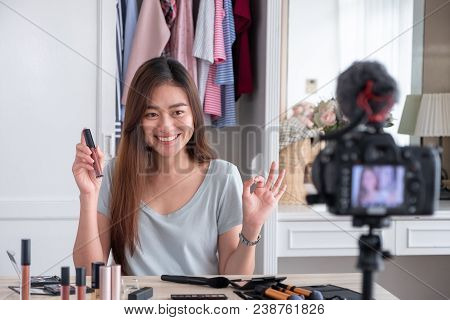 Asian young female blogger recording vlog video with makeup cosmetic at home online influencer on social media concept.live streaming viral stock photo