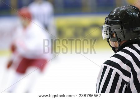 Hockey sport background - rear view of the referee against the blurry hockey game. stock photo