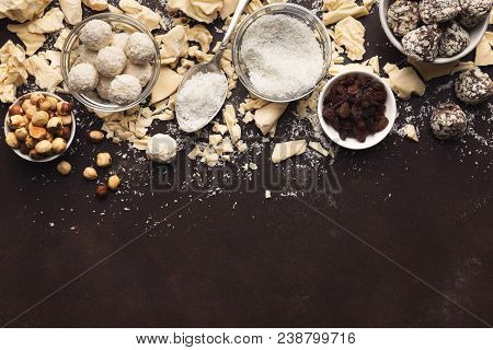 White chocolate chunks on dark background, truffles, raisins, hazelnuts bowls, top view. Confectionery shop advertising and cooking ingredients concept, mockup for homemade candies recipe, copy space stock photo