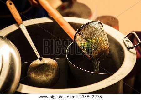 Thai Asian Street Food on rowing boat, fresh white rice Noodle Blanched in Noodle strainer basket with wood handle and warm aluminum stock boiler pot with smoke in soft warm sunset light background stock photo