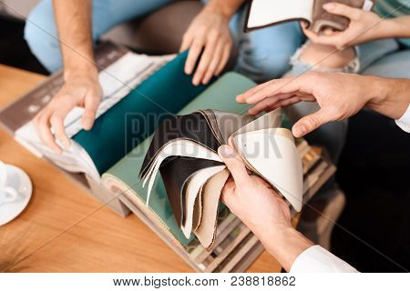 The guy is holding leather samples for the upholstery of the sofa. A young family chooses new furniture for themselves. stock photo