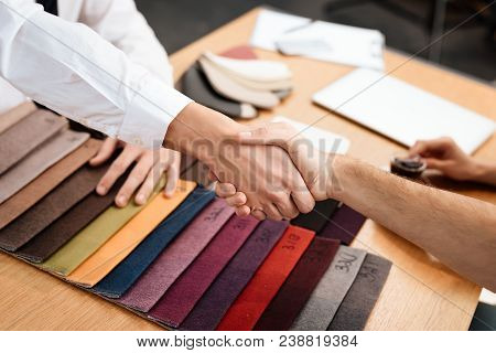 The seller shows samples of materials for furniture. A young couple came to a furniture store. Men shake hands with each other. stock photo