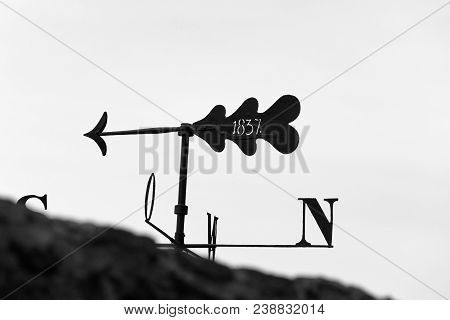 silhouette of an iron weather vane as a compass directions with arrow, and the year 1837 behind a wall, blackwhite stock photo
