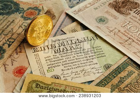 One golden physical Bitcoin coin on the ancient german money. Inflation 1923, one million marks. Cryptocurrency, blockchain and Financial concept background. Close-up, copy space. stock photo