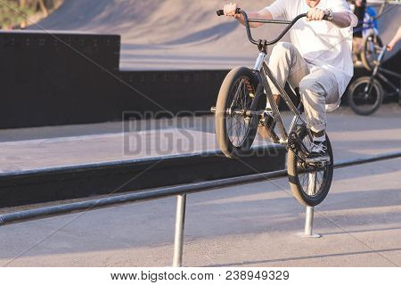 A young man in light clothing slides on the railing on the rear wheel of a BMX bike. Stunts in the skate park on the BMX. BMX concept. stock photo