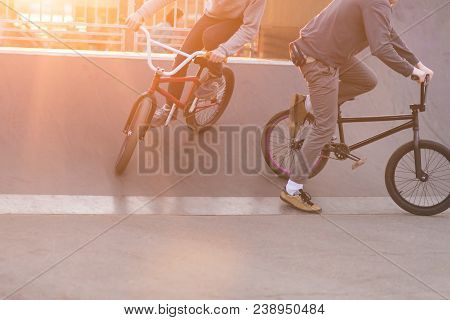 Bmx riders make tricks in a skate park on the background of the sunset. Evening training BMX cyclists. Bmx Concept. stock photo