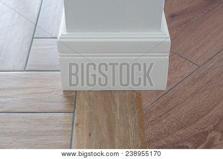 Laminate parquete flooring, tiles immitating hardwood flooring. Cork compensator as an adapter. Light matte wall, white baseboard stock photo