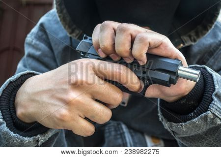 A man holding a gun on his back. The gunman held his gun behind him.Crime Concept.Criminality Concept stock photo
