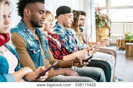 Multiracial friends group on bored moment using smartphone - Addicted people hypnotized by mobile smart phone and social media networks - Technology concept with always connected millennials stock photo