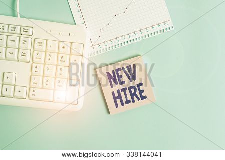 Conceptual hand writing showing New Hire. Business photo showcasing someone who has not previously been employed by the organization Paper blue keyboard office study notebook chart numbers memo. stock photo