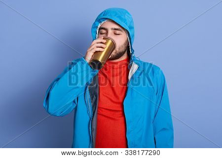 Image of young attractive bearded man poses isolated over blue background, drinks tea or coffee from thermo mug, wears jacket with hood, enjoys hot beverage with closed eyes, moving towards zero waste stock photo