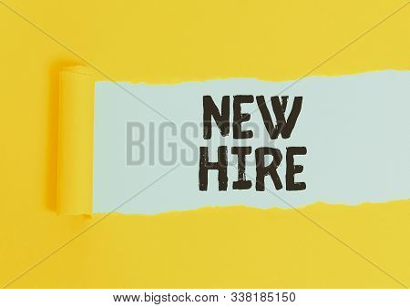 Writing note showing New Hire. Business photo showcasing someone who has not previously been employed by the organization Cardboard which is torn placed above a wooden classic table. stock photo