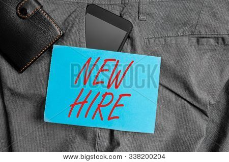 Conceptual hand writing showing New Hire. Business photo text someone who has not previously been employed by the organization Smartphone device inside trousers front pocket with wallet. stock photo