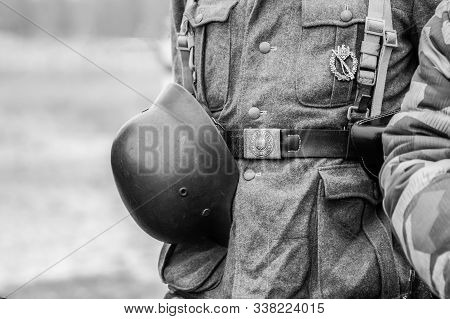 Wehrmacht soldier helmet fastened to his belt closeup. Black and white shot stock photo
