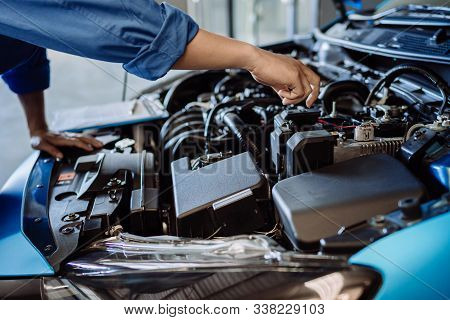 Mechanic man examining and maintenance to customer the engine a vehicle car hood, Safety inspection test engine before customer drive on a long journey, transportation repair service center stock photo