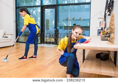 professional cleaning service. Two women in working uniform, in aprons, divide the cleaning of the kitchen of a private house, cottage. Washing floor stock photo