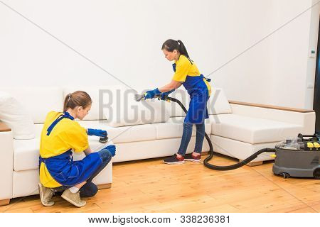 professional cleaning service. Two women in working uniform, in aprons. Two women in working uniform, in aprons, divide the cleaning of private house, cottage. Washing , vacuum cleaning the sofa stock photo