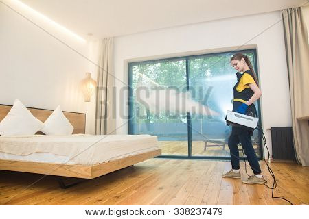 professional cleaning service. woman in uniform and gloves does the cleaning in a cottage. treatment, disinfection of the apartment with hot steam from odors and parasites, bed bugs stock photo