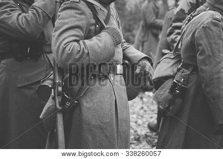 Close up of German military ammunition of a German soldier at World War II. Warm autumn clothes, soldiers overcoat, gloves, helmet, pouch, sapper shovel, flask, rifle, storage box case for gasmask. stock photo