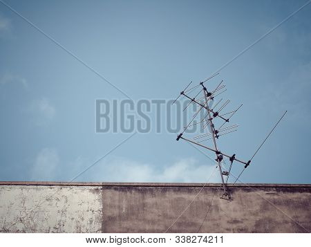 Old analog antenna for TV with blue sky background. Vintage color fitter with place your text. Bangkok, Thailand. stock photo