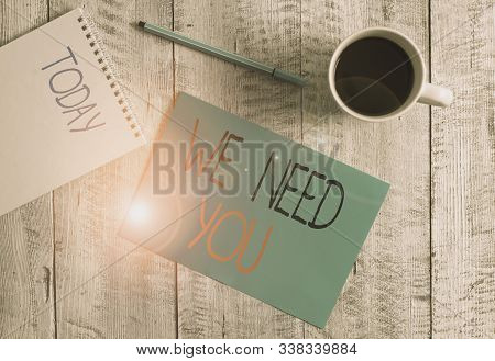 Writing note showing We Need You. Business photo showcasing to fulfill the needs of the assignment duty or obligation Stationary placed next to a cup of black coffee above the wooden table. stock photo