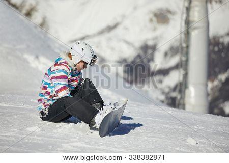 Snowboarder adjusting binding on her equipment stock photo
