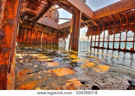 Interior of rusty shipwreck in Greece full of sea water in Glyfada beach near Gytheio, Gythio Laconia, Peloponnese, Greece. stock photo