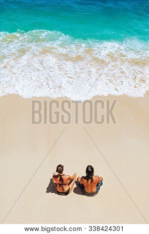 On Sunny Beach Happy Young Couple Relaxing, Sunbathing, Sit On White Sand, See At Sea Surf With Foam