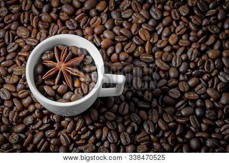 Arabica coffee beans background pattern texture white coffee cup with anise. Coffee cup with beans on black background. Top view arabica & robusta dark beans in cup background for cafe or coffee shop stock photo