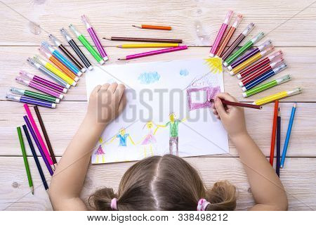 A child draws a birthday card with his family. The drawing was made by a child using colored markers and pencils. Happy family. Children's drawing. View from above. stock photo