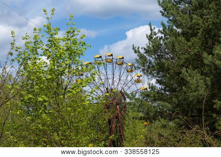 Old broken rusty metal radioactive electric wheel abandoned, the park of culture and recreation in the city of Pripyat, the Chernobyl disaster, Ukraine. stock photo