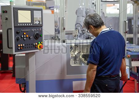 Worker control compact CNC lathe with robotic loading workpiece stock photo
