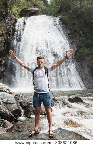 Man at Korbu Waterfall on the Lake Teletskoye in autumn Altai Mountains. stock photo