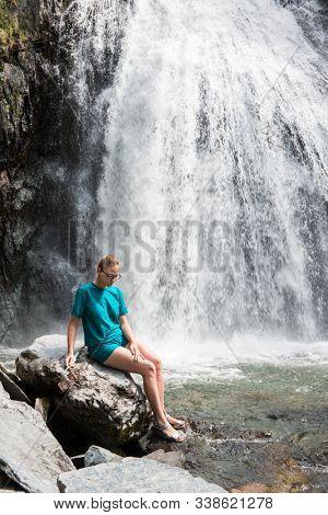 Woman at Korbu Waterfall on the Lake Teletskoye in autumn Altai Mountains. stock photo