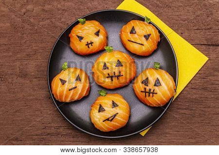 Funny Halloween Sushi Pumpkins Jack o Lantern, Sushi Monsters. Temari sushi, sushi balls. Healthy food for kids. Napkin, old wooden boards background, copy space, top view stock photo