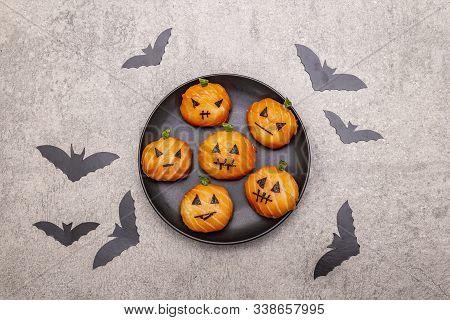 Funny Halloween Sushi Pumpkins Jack o Lantern, Sushi Monsters. Temari sushi, sushi balls. Healthy food for kids. Black bats, napkin, stone concrete background stock photo