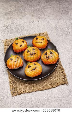 Funny Halloween Sushi Pumpkins Jack o Lantern, Sushi Monsters. Temari sushi, sushi balls. Healthy food for kids. Ceramic plate, sackcloth, stone concrete background, copy space, close up stock photo
