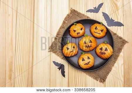 Funny Halloween Sushi Pumpkins Jack o Lantern, Sushi Monsters. Temari sushi, sushi balls. Healthy food for kids. Bats, sackcloth, wooden boards background stock photo