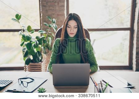 Photo of amazing brunette business lady resourceful person looking seriously notebook on table modern user sitting boss chair wear green turtleneck in modern interior office stock photo