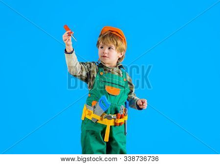 Little boy with helmet and tools. Builder. Kid game. Tools for building. Little repairman. Kid as construction worker. Little boy in builders uniform with tools. Little boy plays construction worker. stock photo