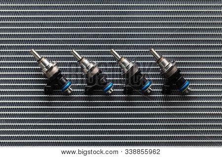 Auto Parts - four fuel nozzles of the injector for the combustion chamber of the engine lie against the background of the patterns of the cooling radiator. stock photo