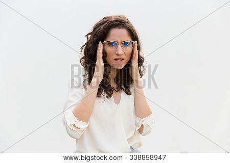 Suspicious worried woman adjusting glasses and staring at camera. Wavy haired young woman in casual shirt standing isolated over white background. Concern concept stock photo