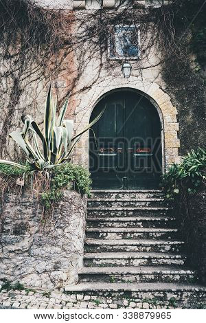 An antique wooden gate in the recess of a stone arch in the wall with a flaked plaster, stony stairs in front, a small lantern on the top surrounded with dry branches, Sintra, Portugal stock photo