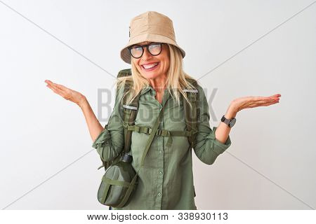 Middle age hiker woman wearing backpack hat canteen glasses over isolated white background clueless and confused expression with arms and hands raised. Doubt concept. stock photo